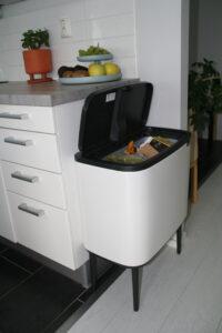 Keittiökaapiston päässä olevan roska-astian sisällä ovat astiat kartonki- ja lasipakkauksille.